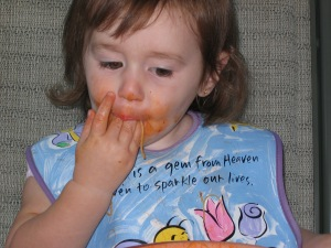 niña pequeña comiendo y chupando su mano