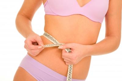 mujer delgada midiendo su cintura
