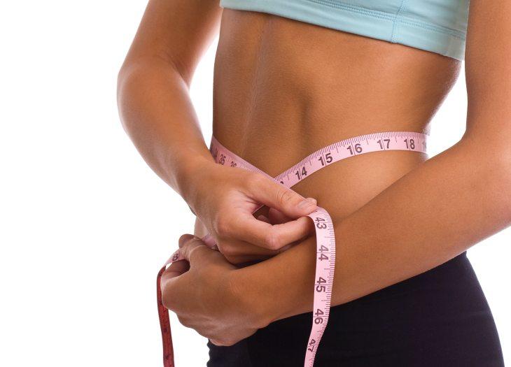 Mujer delgada midiendo su circunferencia de cintura
