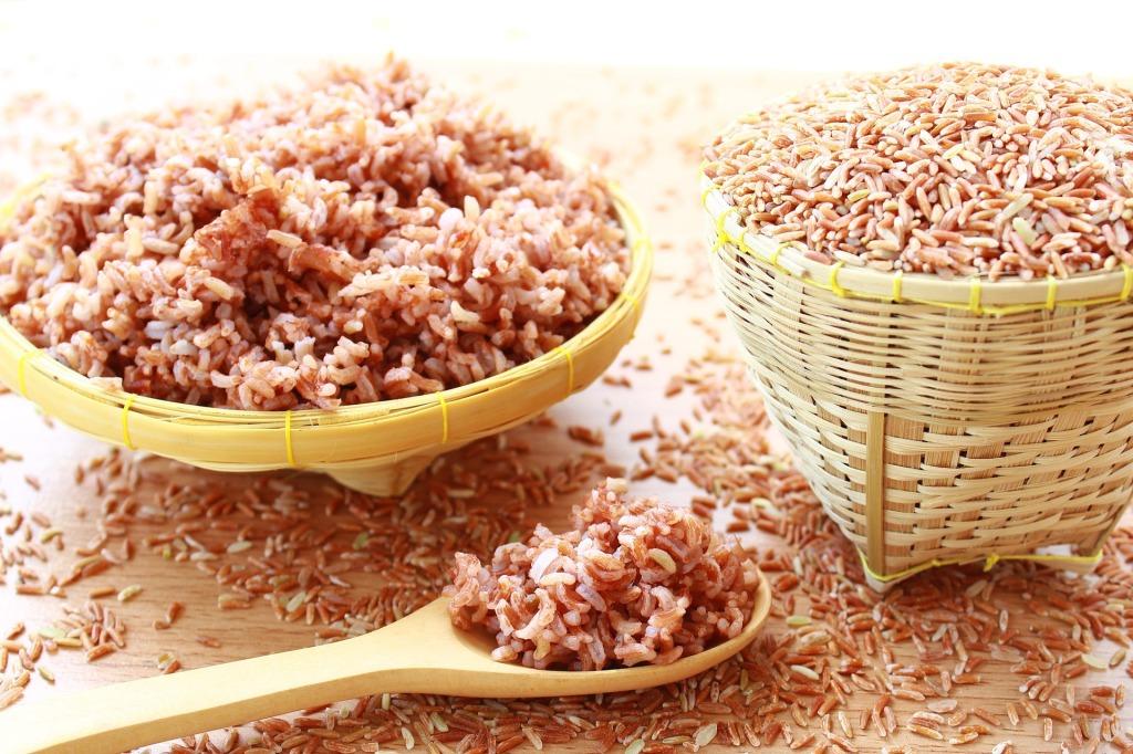 Cesta con granos de arroz integral y plato con arroz integral cocido