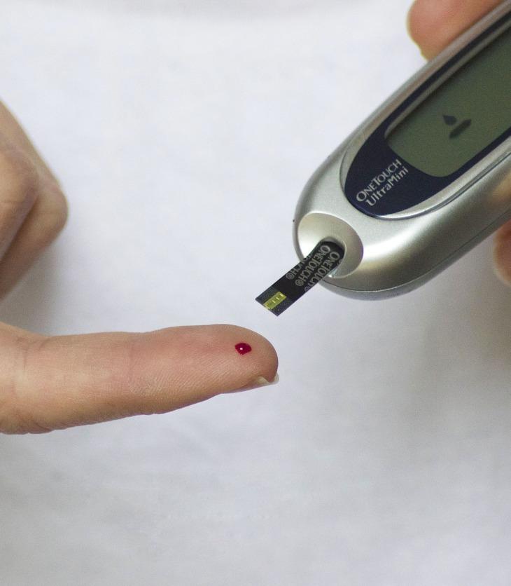 Manos de una persona midiendo su glucosa con un glucómetro