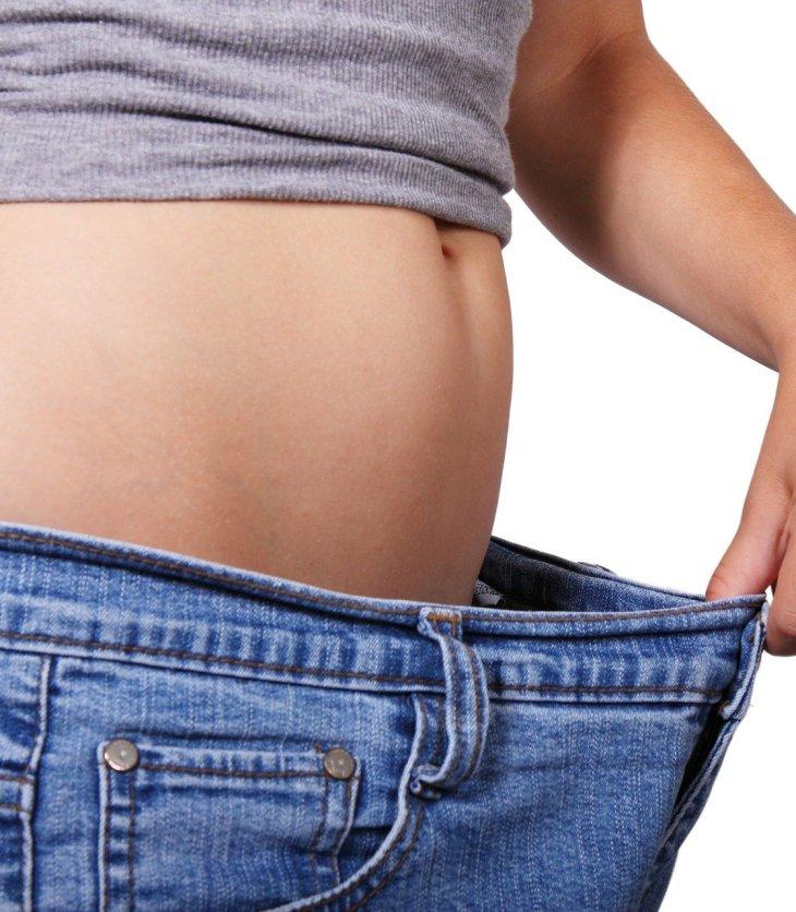 Mujer que ha bajado de peso muestra un pantalón que le queda grande en la cintura