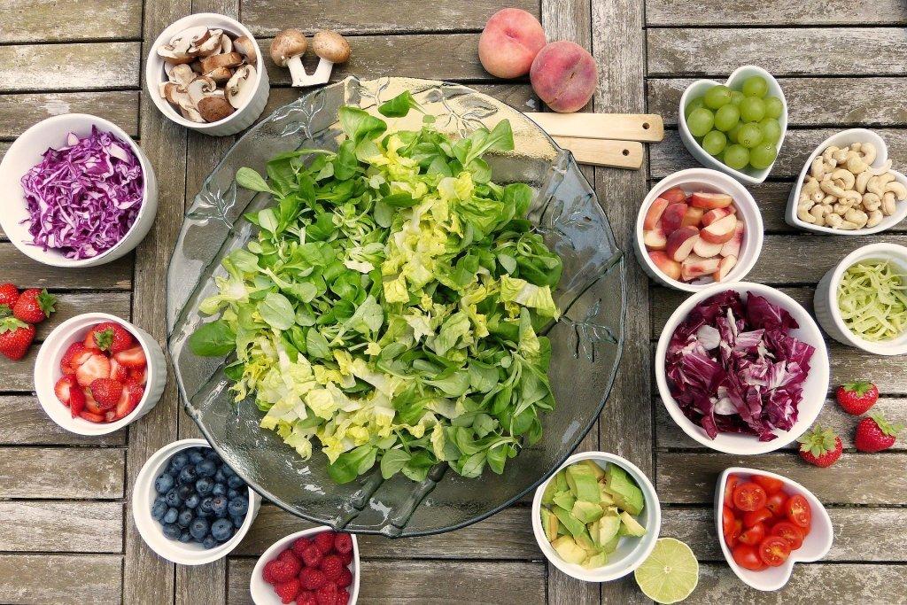 Tazones de diferentes tamaños con ingredientes para preparar ensalada de verduras y frutas