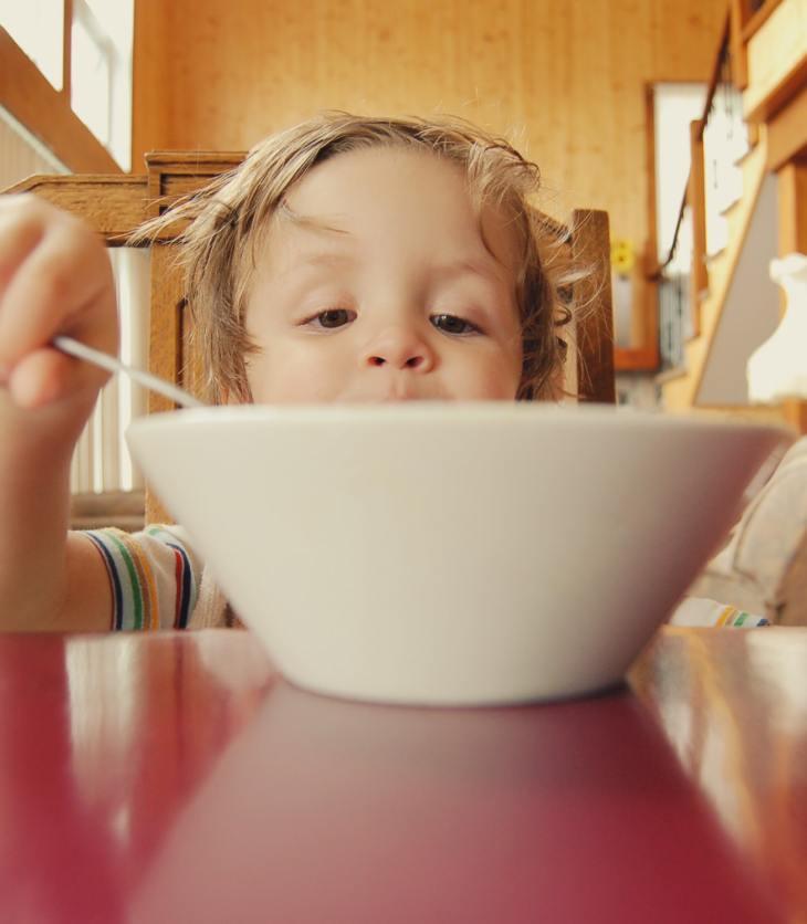 Niño preescolar comiendo de un gran tazón