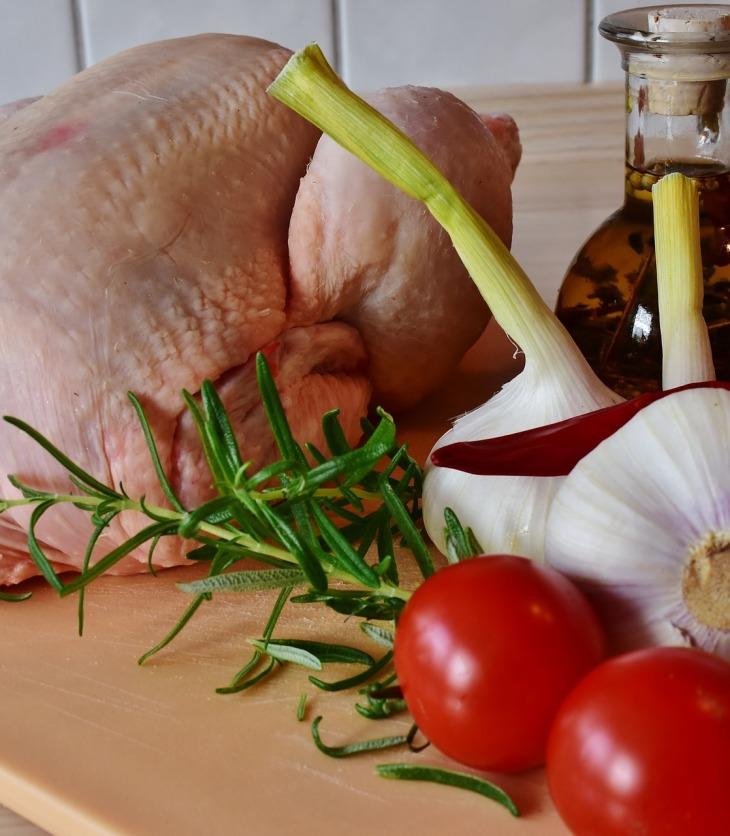Pollo crudo, ajos y tomates sobre una tabla de picar