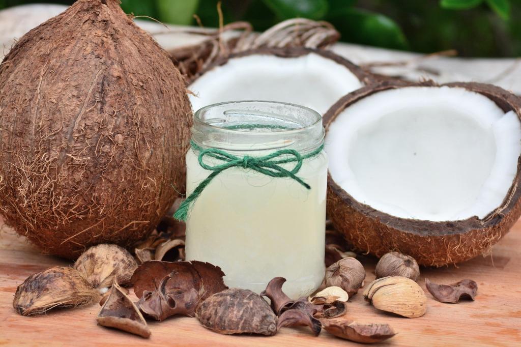 Coco natural partido y frasco con aceite de coco