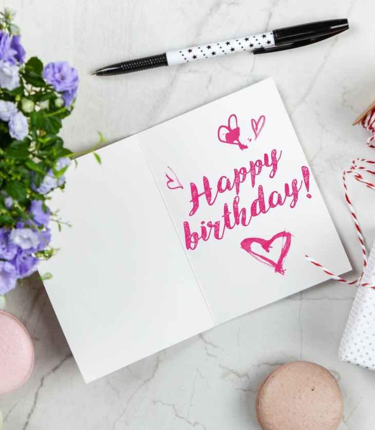 Tarjeta de felicitación de cumpleaños junto a un jarrón con flores