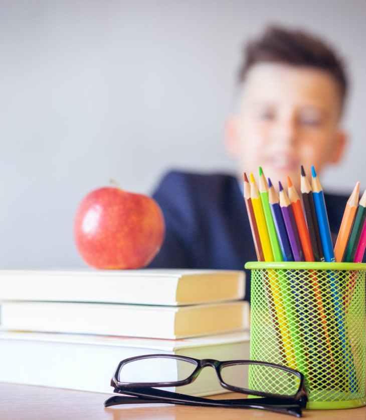 Niño detrás de un escritorio con libros, lápices y una manzana