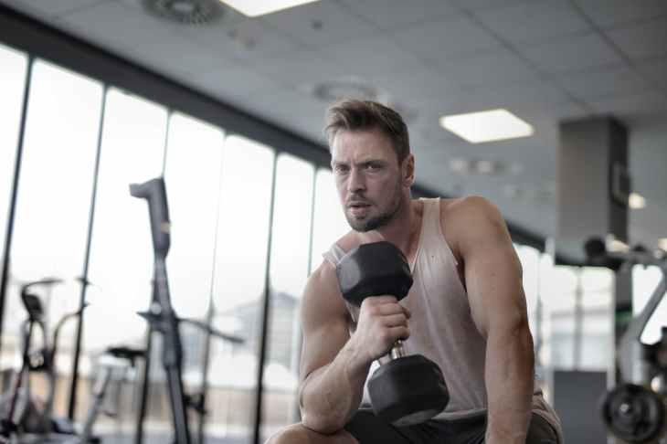 Hombre musculoso haciendo ejercicio con mancuerna en un gimnasio