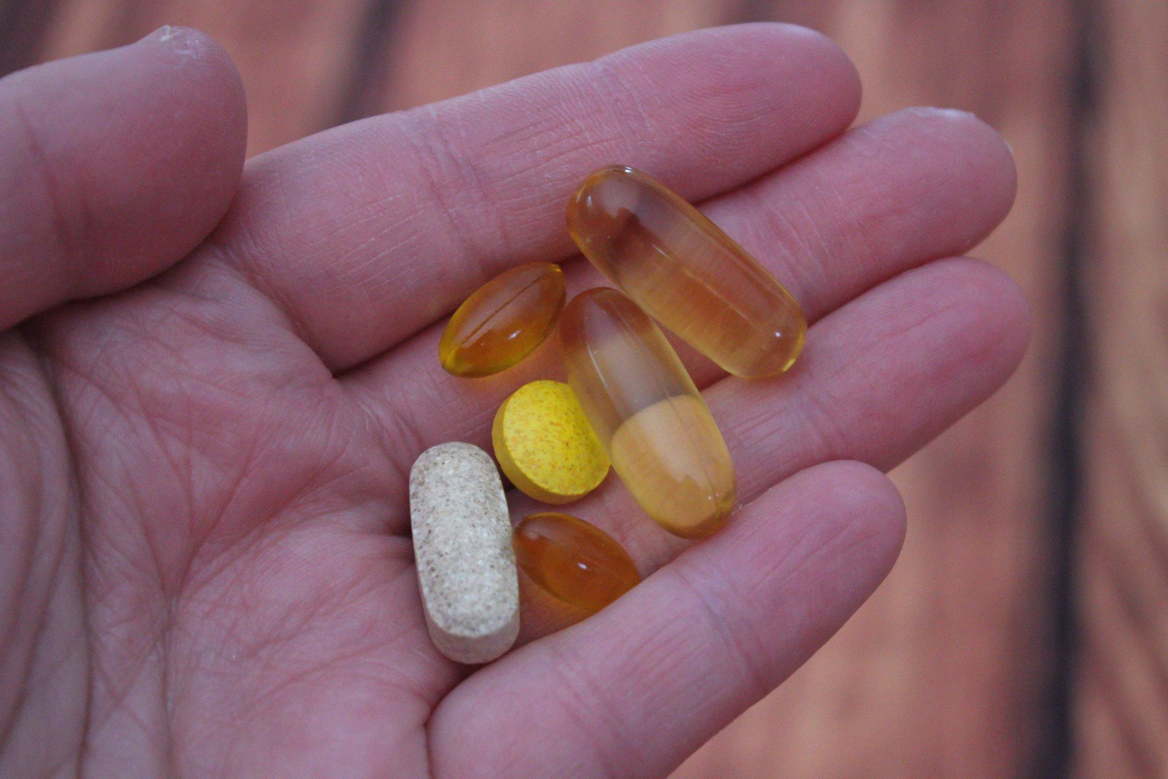 Mano mostrando suplementos de cúrcuma en cápsulas y tabletas